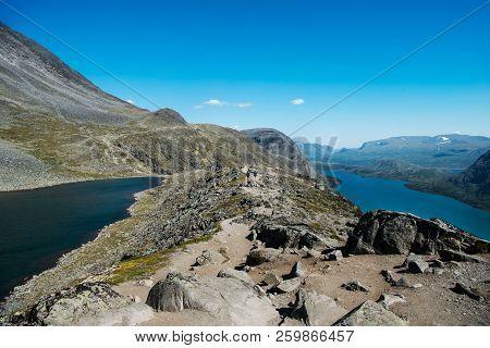 People Hiking On Besseggen Ridge Over Gjende Lake In Jotunheimen National Park, Norway