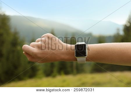 Woman Checking Smart Watch With Blank Screen In Wilderness, Closeup