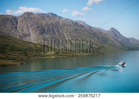 Boat Floating On Calm Water Of Majestic Gjende Lake, Besseggen Ridge, Jotunheimen National Park, Nor