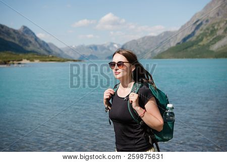 Beautiful Young Woman In Sunglasses With Backpack Standing Near Majestic Gjende Lake, Besseggen Ridg