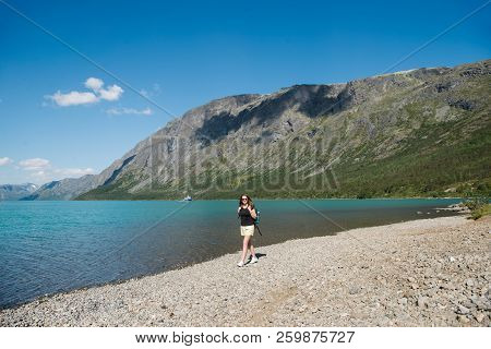 Beautiful Young Woman With Backpack Walking Near Gjende Lake, Besseggen Ridge, Jotunheimen National