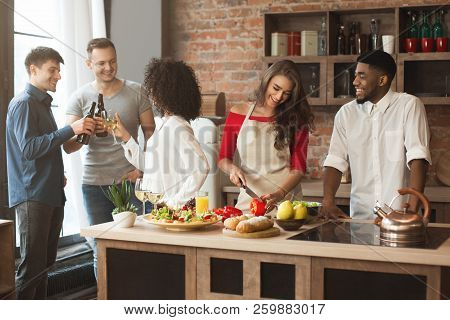 Group Of Multiracial Friends Cheering While Cooking Dinner At Kitchen.
