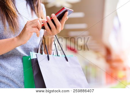 Woman Holding Shopping Bags Doing Online Shopping On Her Mobile Phone In The Supermarket. Black Frid