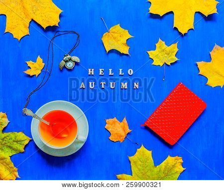 Fall still life. Cup of tea, maple fall leaves, metal clock, red notebook and inscription Hello autumn on the bright blue background. Fall seasonal composition