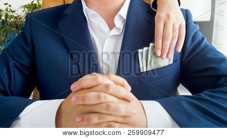 Closeup Photo Of Female Hand Stealing Money From Businessman's Pocket
