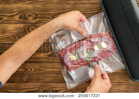 Unidentified Adult Man Sliding Plastic Packaged Meat With Onion And Garlic Into Black Machine To Pre
