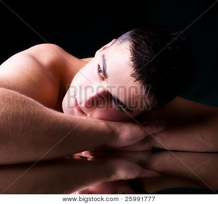 muscular young man lying on his hands, studio shot