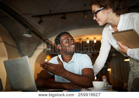 Young businessman pointing at laptop screen while explaining what he thinks about the data to his colleague
