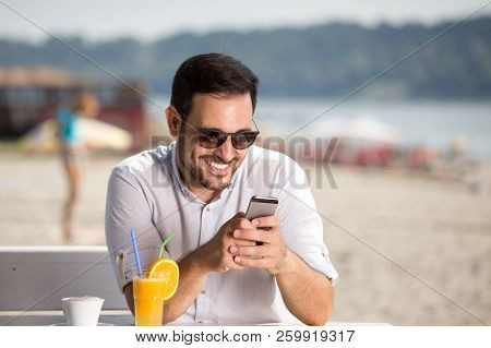 Man Enjoying Morning Coffee On River Beach