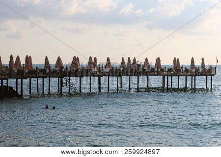 The Pier Near Sea. Wooden Pier With Sunbeds.