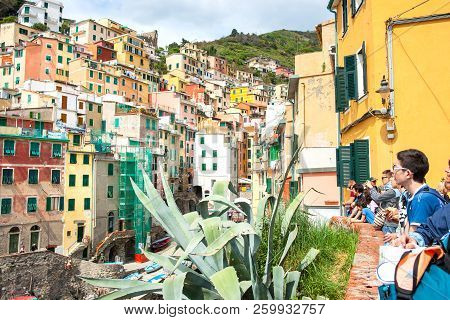 Riomaggiore Italy -april 26 2011; Young Travelers Looking From One Valley Sie To Other With Rows Of