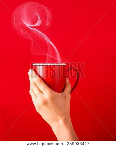 Woman with a cup of fragrant coffee in her hands on a cool day. Black warm coffee in cold weather.Coffee on a red background for your design. Advertising coffee.