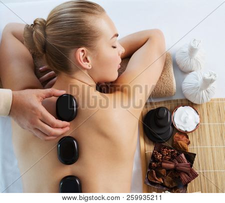 Young woman getting hot stone massage in spa salon. Beauty treatment concept. The girl's relaxing on spa procedures.