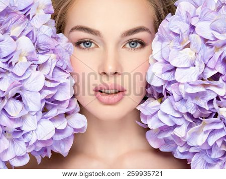 Beautiful young blonde woman with flowers near face -isolated on white. Pretty model  cares of a face. Caucasian girl with blue eyes.