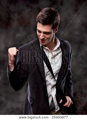 Champion business man standing with fists clenched in victory. Studio shot