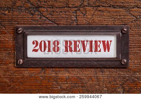2018 review - a label on grunge wooden file cabinet. A passing year summary and review concept.