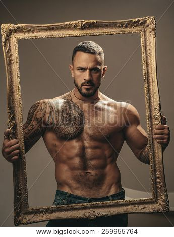 Latin Man With Muscular Body Holds A Frame And Looks Seriously. Muscular Latin Lover. Handsome Bruta