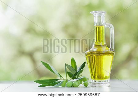 Olive Oil In Glass Bottle Outdoor Against Natural Olive Trees Background.