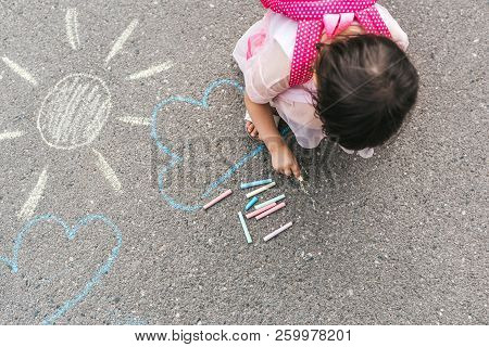 Top View Image Of Happy Little Girl Wears Pink Dress And Backpack Drawing With Colorful Chalks On Th