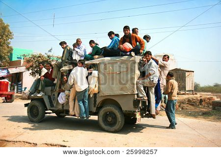 AGRA, INDIA - FEBRUARY 22:  Public transport in India .Crazy road scene -truck with many people.   February 22, 2008. , Agra,  India.