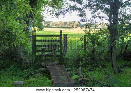 A wooden stile with a way sign on a public right of way on the Gower Peninsula in South Wales, UK.