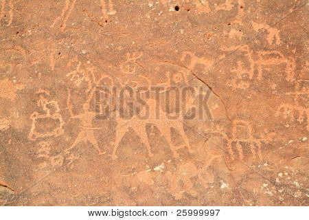 Images of people and camels carved into a rock wall at Wadi Rum, a UNESCO World Heritage site in Jordan. poster