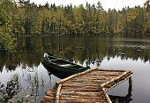 boat, like a gondola tied at a wooden pier on the lake, forest in the background, tempting mystical atmosphere, outdoor recreation, autumn poster