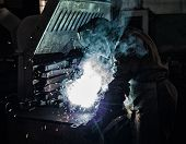 Welder welds metal parts, lots of smoke and sparks, harmfulness, manufacturing poster