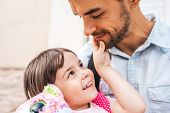 Closeup portrait of handsome happy young father embrace his daughter after preschool day. Cute little girl looking to his dad smiling and playing with dad feeling happy. Fatherhood concept poster