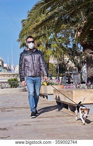 Coronavirus. Man With Face Mask Walking With Dog During Coronavirus In Park. Short Walks During Covi