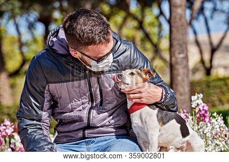 Man Wearing Face Mask Kissing Dog During Coronavirus. Short Walks During Covid-19 Pandemic. Avoid Co