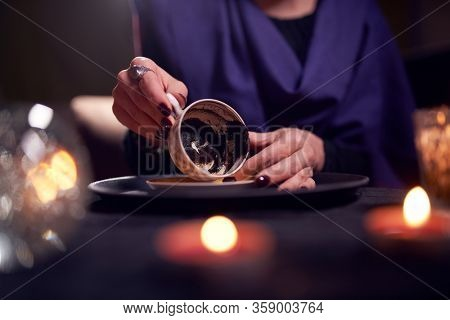 Close-up of fortuneteller's hands divining on coffee grounds at table with predictive ball