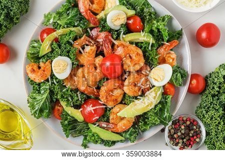 Shrimp Caesar Salad With Avocado, Parmesan Cheese, Tomatoes, Eggs And Kale On White Marble Table. To