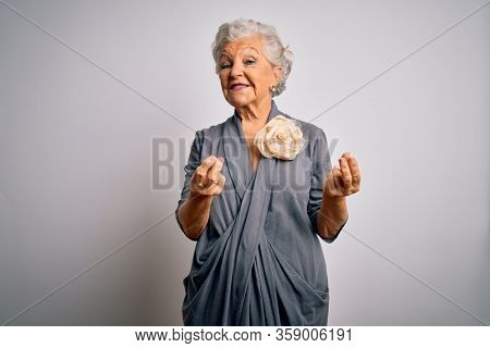 Senior beautiful grey-haired woman wearing casual dress standing over white background doing money gesture with hands, asking for salary payment, millionaire business