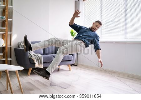 Man Slipping And Falling On Wet Floor At Home