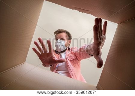Man In A Medical Mask Unboxing Inside View A Delivered Box, Shows A Stop Gesture With Hands Afraid O