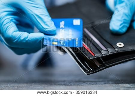 Consumer Holding Credit Card In Gloves To Protect From Coronavirus