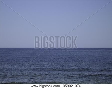 The Flat Line Of The Sea Horizon Between The Cloudless Sky And The Blue Calm Sea On A Clear Sunny Da
