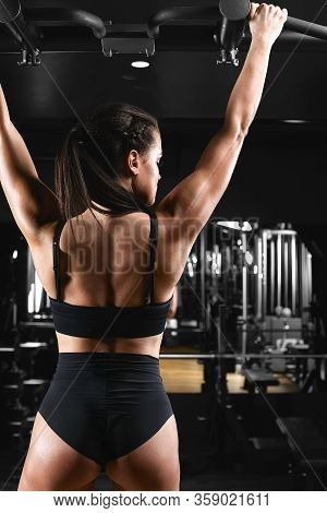 Woman Working Out In Gym - Pull Ups. Image Cross Processed, Contrasty, Dark Grainy Image.