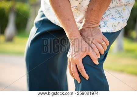 Asian Old Woman Walking In Park And Having Knee Pain, Knee Injury In Park. Senior Healthcare Concept
