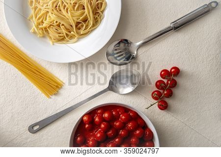 Stainless Steel Spoon And Ladle Between Serving Of Pasta And Bowl Of Tomato Sauce