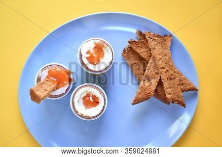 Three Peeled Soft-boiled Eggs In Egg Cups And Slices Of Toast On A Blue Plate Over A Yellow Backgrou