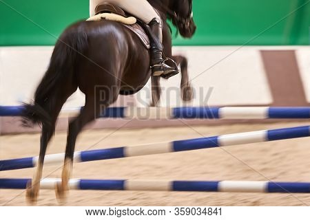 Rider On A Black Horse Jumps Over An Obstacle, Motion Blur. Focus On The Riders Boot.