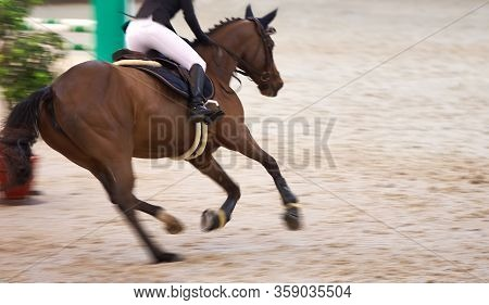 A Rider On A Beautiful Brown Horse Rides Around Obstacles, Motion Blur, Focus On The Riders Boot.