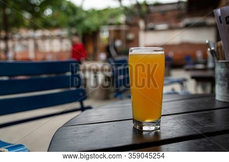 Full Juicy Ipa Beer In Pint Glass On Picnic Table At A Restaurant