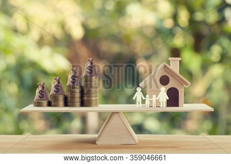Property Investment And House Mortgage Concept: Wooden Home, Family Member And Us Money Bags On Rows