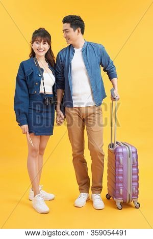 Traveler Asian Couple With Backpack And Suitcase Standing Isolated Over Yellow Background. Couple As