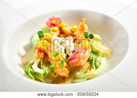 Warm salad with crispy langoustines. Delicious served dish with roasted seafood. Tasty food in white plate decorated with flowers and sauce. Haute cuisine, sicilian recipe. Restaurant menu