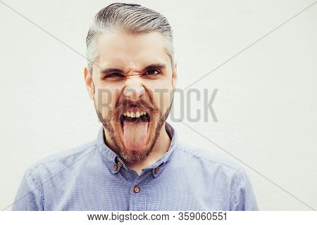 Joyful Funny Man Grimacing And Sticking Out Tongue. Grey Haired Young Man In Blue Casual Shirt Posin