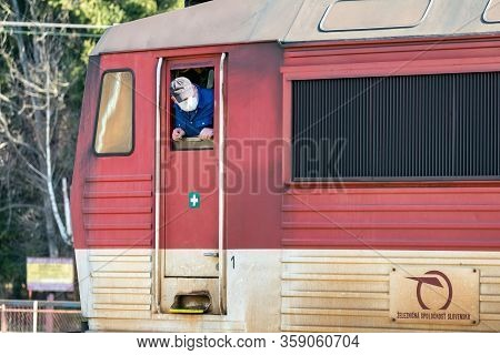Ruzomberok, Slovakia - April 1, 2020: Driver Of Locomotive With Face Looking From Dirty Train